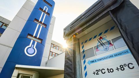 Außenansicht des Pharma Hubs: Auf runtergelassenen Toren steht die Temperaturangabe 2 bis 8 Grad Celsius.
