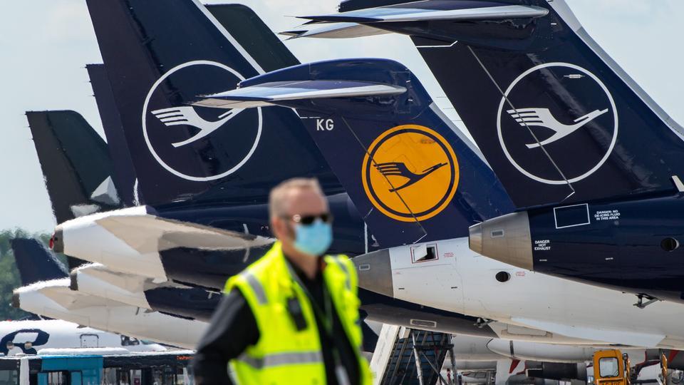 Ein Mann mit Mundschutzmaske steht vor Lufthansa-Maschinen,