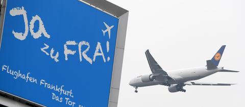"""Lufthansa-Flugzeug in der Luft - auf einer Anzeigentafel """"Ja zu FRA"""""""