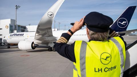 """Ein Mann mit einer Weste mit der Aufschrift """"LH Crew"""" fotografiert einen Airbus A350-900 nach der Landung."""