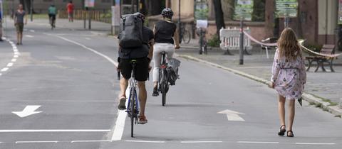 Fußgänger und Radfahrer auf dem für den Autoverkehr gesperrten Mainkai in Frankfurt