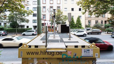 Im Vordergund ist eine Luft-Messstation an der Friedberger Landstraße in Frankfurt zu sehen. Im Hintergund viele fahrende, deshalb unscharfe, Autos .