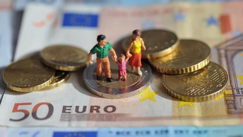 Sujetbild: Eine Spielzeugfamilie steht auf Geldscheinen