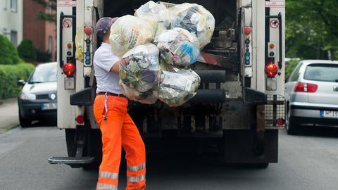 Müllwerker wirft Abfallsäcke in Auto