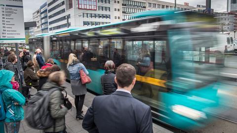 Fahrgäste an einer Haltestelle für Busse und Straßenbahnen an der Konstalberwache in Frankfurt