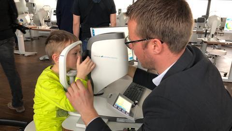 Ein Junge blickt in ein Optik-Diagnosegerät.