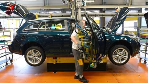 Ein Arbeiter im Opelwerk Rüsselsheim montiert Teile an einem Insignia