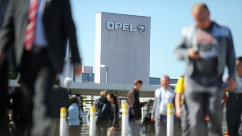 Menschen vor dem Opel-Turm in Rüsselsheim.