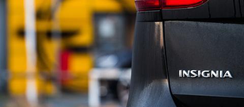 Ein Auto mit dem Schriftzug Insignia vor einem Opel-Logo.