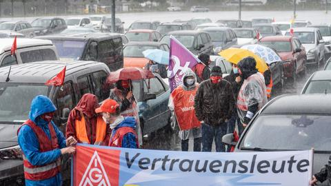 In strömendem Regen demonstrieren Mitarbeiter am Stammsitz des Autobauers Opel in Rüsselsheim gegen zunehmenden Druck an ihren Arbeitsplätzen. Angereist waren offenbar auch Kollegen aus dem Standort Eisenach.