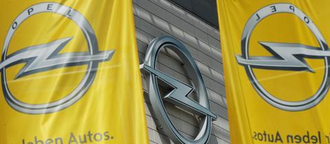 Opel-Fahnen vor einem Opel-Logo.