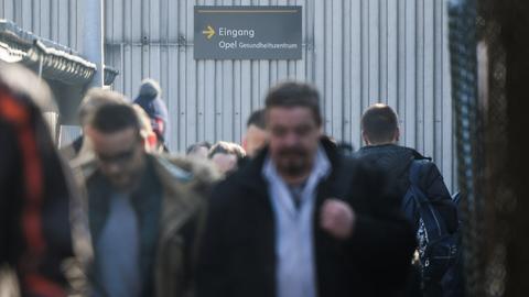 Opel-Mitarbeiter verlassen beim Schichtwechsel in Rüsselsheim das Werk.