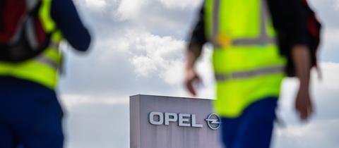 Zwei Männer in gelben Sicherheitswesten gehen in Rüsselsheim am Stammwerk von Opel vorbei