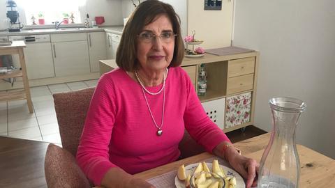 Osteoporose-Patientin Margit Weimer sitzt in ihrer Wohnung am Tisch un schält sich einen Apfel.