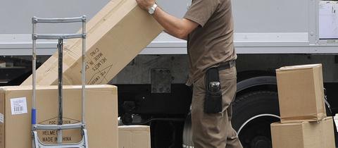 Bote mit zahlreichen Paketen neben geöffnetem Lieferwagen
