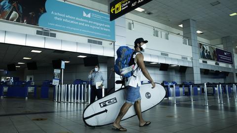 Ein Passagier geht mit seinem Surfbrett zum Check-in am internationalen Flughafen Tocumen in Panama-Stadt.