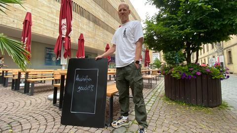 """Auf einem Schild steht: """"Aushilfen gesucht"""" für die Gastronomie."""