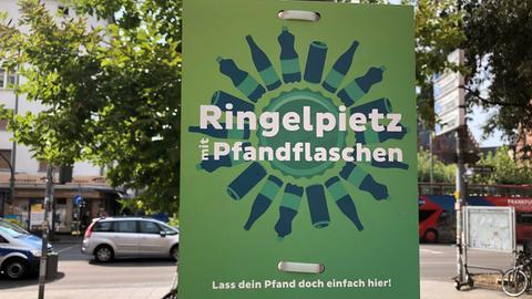 """Ein Schild wurde aufgestellt mit der Aufschrift: """"Ringelpietz mit Pfandflaschen""""."""