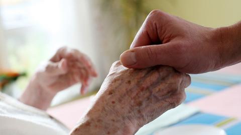 Die Hand einer jungen und einer alten Person greifen in einem Krankenhaus ineinander.