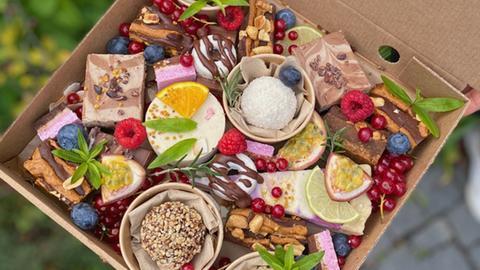 Zu sehen sind einige bunte Kuchen und Torten in einer Schachtel zum Mitnehmen.