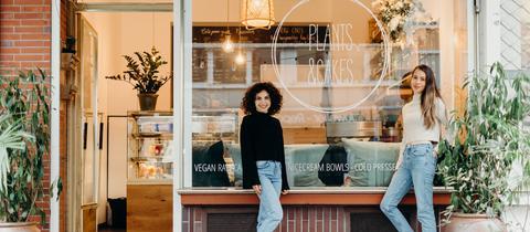 """Sibel Bakanhan und Angela Lederer stehen vor ihrem Café """"Plants & Cakes"""". Zu sehen ist das kleine Café mit Sitzmöglichkeiten"""