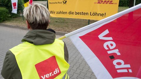 Eine Frau mit Verdi-Flagge vor einem Post-Plakat.