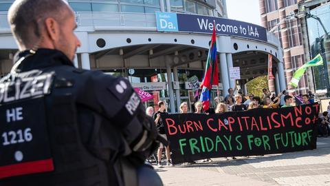 """Ein Polizist beobachtet junge Demonstranten von """"Fridays for Future""""."""