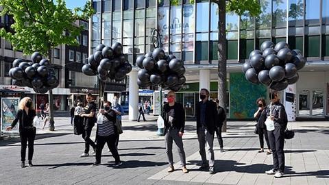 Beschäftigte stehen mit schwarzen Luftballons vor der Kasseler Galeria Kaufhof Filiale