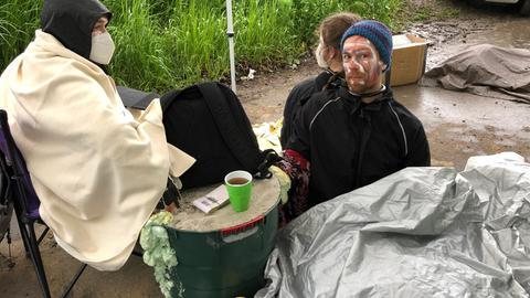 Tierschutz-Aktivisten haben sich auf einer Zufahrt zu Plukon mit Eimern voll Gips fixiert.