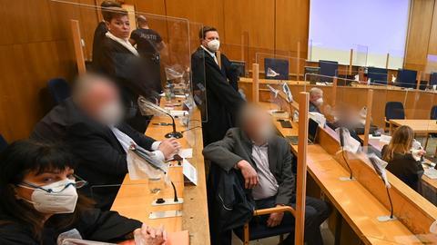 """Drei frühere Mitarbeiter der inzwischen insolventen Maple Bank mit ihren Anwälten im """"Cum-Ex""""-Verfahren auf der Anklagebank."""