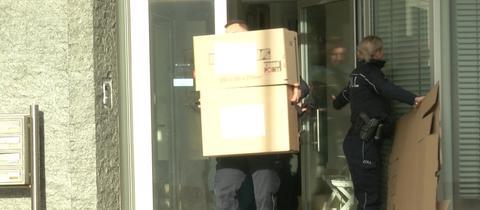 Zwei Zollbeamte tragen Kisten aus einer Wohnung.