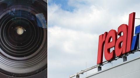 Schild eines Real-Supermarkts und Kamera-Objektiv