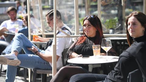 Getrennt von provisorischen Holzgerüsten mit Kunststoffscheiben genießen die Gäste eines Lokals in der Frankfurter Freßgass ihre Getränke.