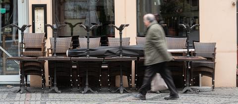 Ein Mann läuft an geschlossenem Restaurant vorbei