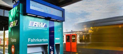 Ein Fahrkartenautomat des RMV in Friedrichsdorf. Im Hintergrund fährt eine Regionalbahn vorbei.