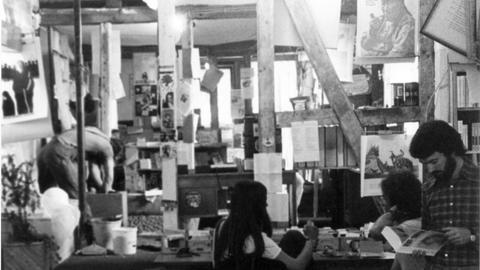 Schwarz-Weiß-Bild von Ladeninnerem, junge Leute lesen, viele Poster und Zettel an den Wänden