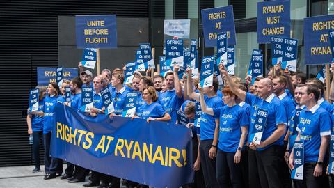 Streikende Ryanair-Piloten in T-Shirts mit Streikslogan mit Transparenten
