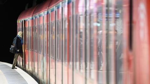 Eine S-Bahn steht an einem unterirdischen Gleis, eine Fahrgast steigt ein.