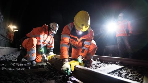 Arbeiter schleifen eine Schiene im Tunnel.