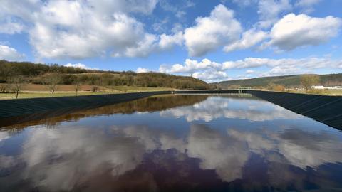 Wolken spiegeln sich in einem Wasserbecken in grüner Landschaft
