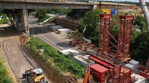 Ein Gerüst wird mit einem ferngesteuerten Kran unter die Brücke geschoben.