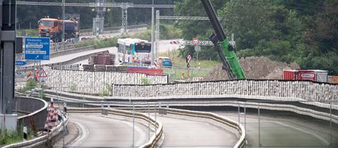 Foto der gesperrten Salzbachtalbrücke am Montagmorgen. Blick in den Straßenverlauf, es sind viele Gitter und Kräne zu sehen.