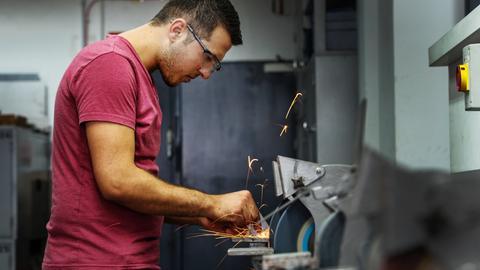 Ein 23-jähriger Syrer bearbeitet bei der Firma Samson an der Schleifmaschine ein Metallstück. Die Firma Samson hat für den Ausbildungsstart im September extra Ausbildungsplätze für Flüchtlinge geschaffen.