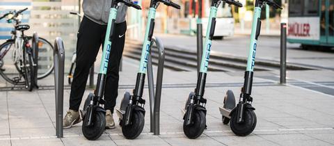 E-Tretroller in Frankfurt - ein Mann entsperrt einen von vier Rollern mit seinem Smartphone.