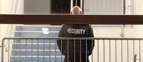 """Ein Mann mit """"Security""""-Jacke im Treppenhaus."""