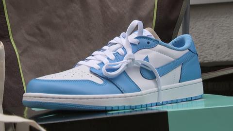 Ein neuer Sneaker steht im Schuhladen auf einem Schukarton.
