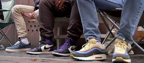 Füße, die in Nike Sneakers stecken