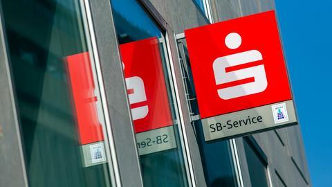Ein Leuchtschild eines Sparkasse SB-Service an einer Fassade spiegelt sich in der Glasfläche.