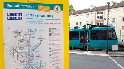 Eine Info-Tafel zur Streckensperrung, in Hintergrund fährt eine U-Bahn.