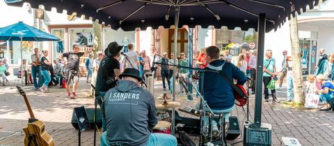 Straßenmusiker - eine Band von hinten aufgenommen - davor steht Publikum - in der Fußgängerzone in Hanau